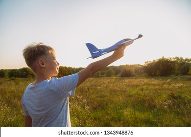 Young happy kid playing blue plastic toy plane outside on summer sunset grassy hill. Horizontal color photography.