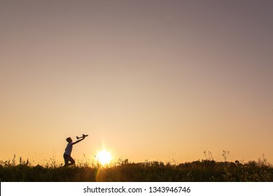Young happy kid playing toy plane outside on summer sunset grassy hill. Horizontal color photography.