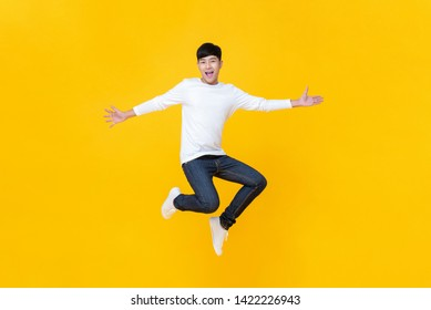 Young happy Korean teen jumping welcomely isolated on yellow studio background