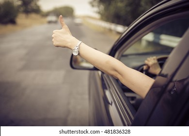 Young happy lady driving a car and making Like /  Ok sign with hand out of window. Girl driving and enjoying road trip and travel, toned with soft autumn colors.
