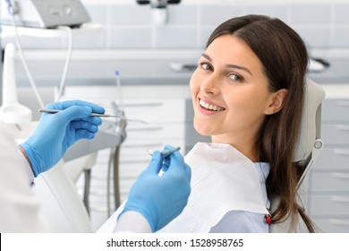 Young happy lady sitting in dentist chair, making regular check up in modern clinic, close up, free space