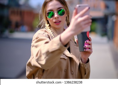 Young happy lady in a spring vacation, walking in the city, drinking coffee, photographing herself on a sunny day