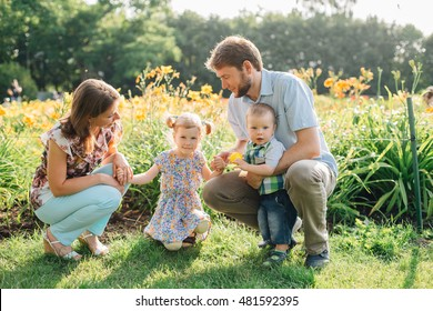 Young happy laughing family having fun in the park. Parents holding their cute children. Couple in love with kids.  Mother father daughter son smiling