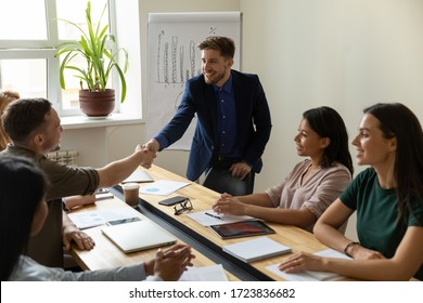 Young happy leader shaking hand with businessman for congratulation success presentation new project. Smiling successful male worker handshaking on flip charts background in boardroom at meeting.