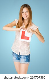 Young happy learner driver holding L-plate.