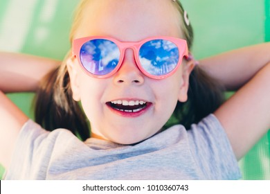 Young Happy Little Girl Lying In Hammock and looking at the sky