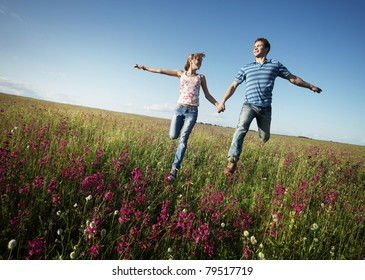 Young happy lovers running on meadow with green grass and pink flowers on a blue sky
