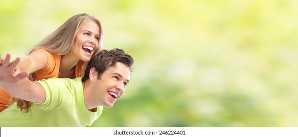 Young happy loving couple over green summer background
