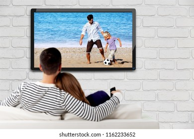 Young happy loving couple sitting on sofa indoors and watching TV.