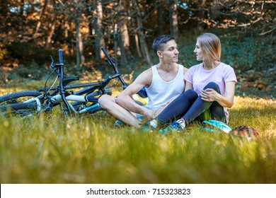 Young Happy Loving Couple. Walking in the park on bicycles. Communication.