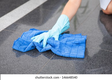 Young Happy Maid Cleaning The Floor With Cloth