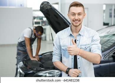 Young happy male car owner smiling showing thumbs up at the garage professional mechanic working on his car on the background copyspace service automobile transport quality repairing gesture concept