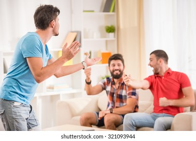 Young happy male friends have fun at home