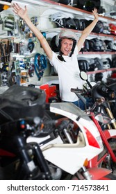 Young happy male sitting on the bike in helmet in the shop