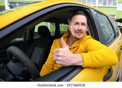 Young happy male taxi driver sits behind the wheel of a taxi and shows like