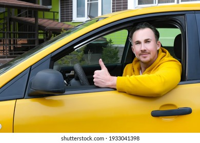 Young happy male taxi driver sits behind the wheel of taxi and shows like