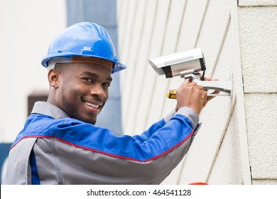 Young Happy Male Technician Repairing Camera With Screwdriver