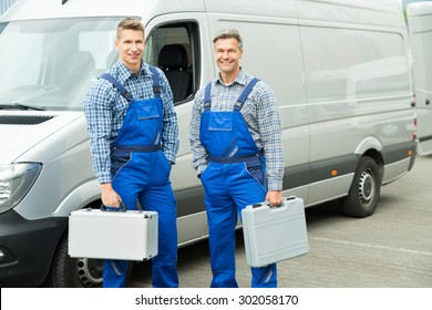 Young Happy Male Worker With Toolbox Standing In Front Of Van
