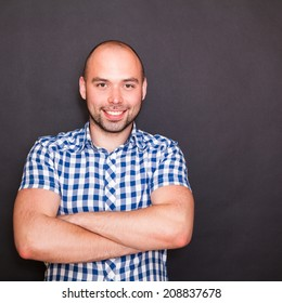 Young happy man against the black background