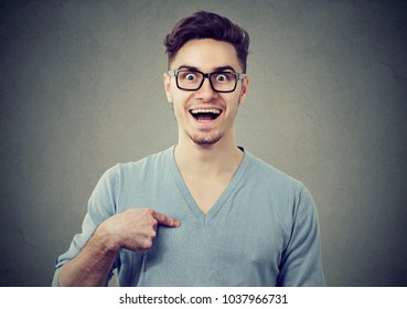 Young happy man amazed with prize pointing at himself in disbelief.