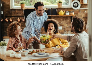 Young happy man bringing salad at dining table while having lunch with friends at home.