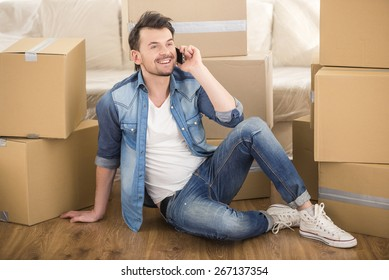 The young happy man calling transport company to move in new house.