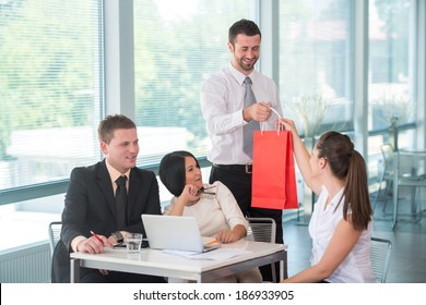 Young happy man handing a red paper bag to a female colleague in office