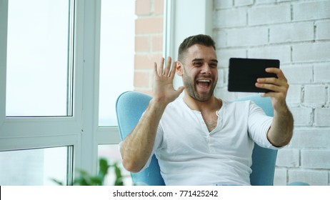 Young happy man have online video chat using digital tablet computer sitting on balcony in modern loft apartment