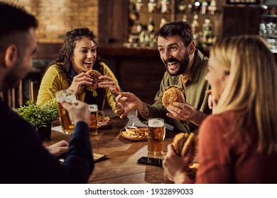 Young happy man having fun with is friends while eating hamburgers and drinking beer in a pub.