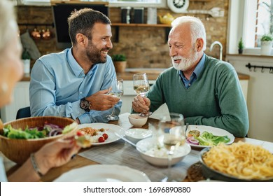Young happy man and his mature father toasting with wine while having lunch in dining room.