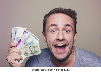 Young happy man holding different currency bills.