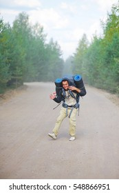 Young happy man in hoodie with heavy backpack and two travel rugs is on road through forest, waving his hands and laughing merrily. Hiking in the woods. Sport and concept of a healthy lifestyle.
