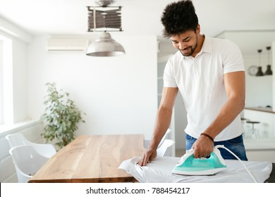 Young Happy Man Ironing Clothes