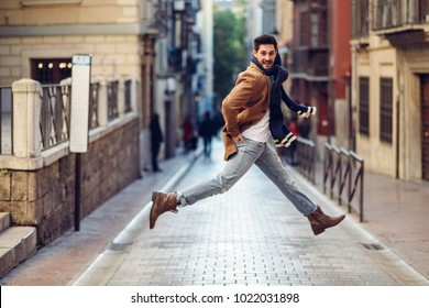 Young happy man jumping wearing winter clothes in the street. Young bearded guy with modern hairstyle with coat, scarf, blue jeans and t-shirt in urban background.