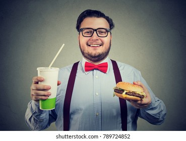 Young happy man looking excited while having burger and soda looking at camera.
