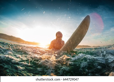 Young happy man moves through breaking waves in the ocean with his surf board and makes a lot of splashes