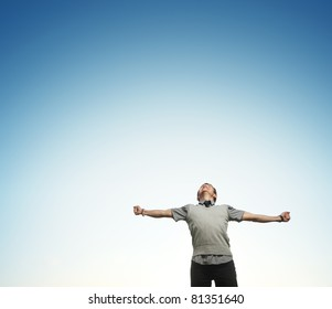 Young happy man on blue sky background with raising hands and looking to a sky
