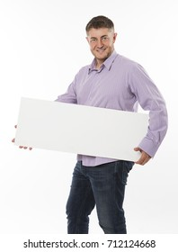 Young happy man portrait of a confident businessman showing presentation, pointing paper placard gray background. Ideal for banners, registration forms, presentation, landings, presenting concept.