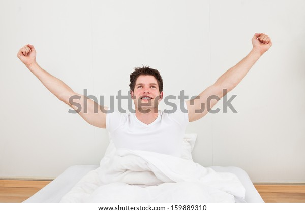 Young Happy Man Raising Arm Sitting On Bed