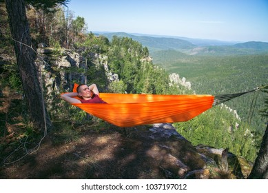 Young happy man relaxing lying in hammock on top of mountain. Summer travel lifestyle.