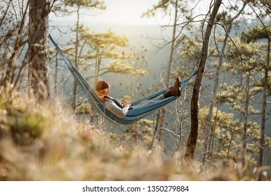 Young happy man relaxing lying in hammock on top of mountain.