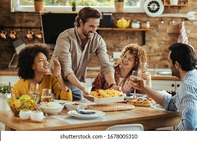 Young happy man serving food at dining table while having lunch with friends at home.
