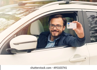 young happy man showing his new driver license