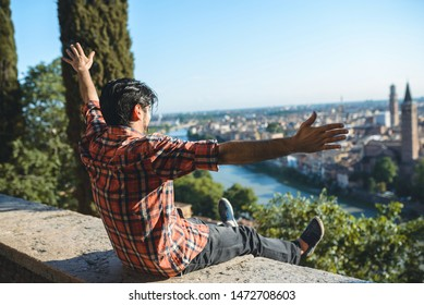 young happy man sitting with hands up with river view