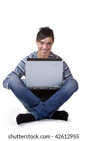 Young happy man sitting on floor and working on laptop. Isolated on white.
