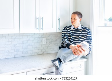 Young happy man sitting on modern new kitchen countertop by window smiling