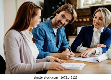 Young happy man talking to his wife while signing a contract on a meeting with insurance agent.