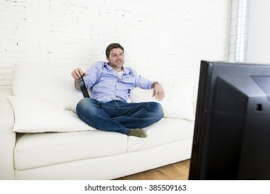 young happy man watching tv lying at home living room sofa with remote control looking relaxed smiling and laughing enjoying television program  comedy movie or sitcom