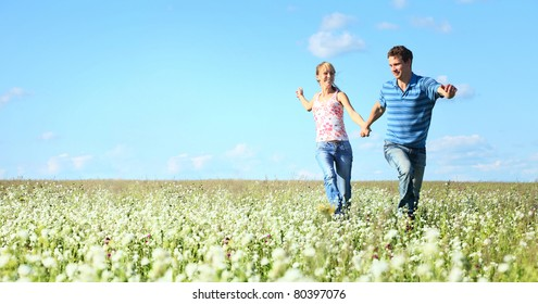 Young happy man and woman running on meadow with fluffy dandelions on blue sky background