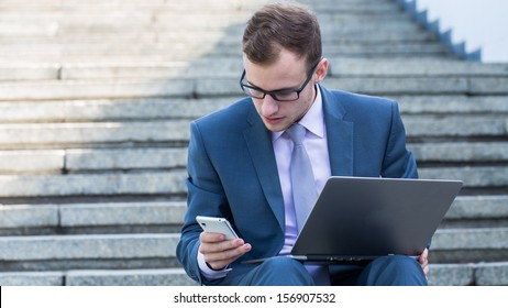 Young happy man working with mobile phone and tablet, horizontal portrait.